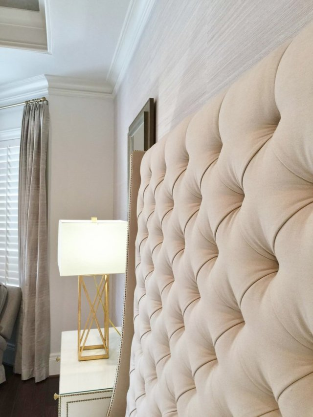 Detail of tufted headboard with grasscloth wallcovering and gilded lamp, Designer: Carla Aston